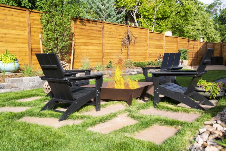 Square copper fire pit with four black adirondack chairs around