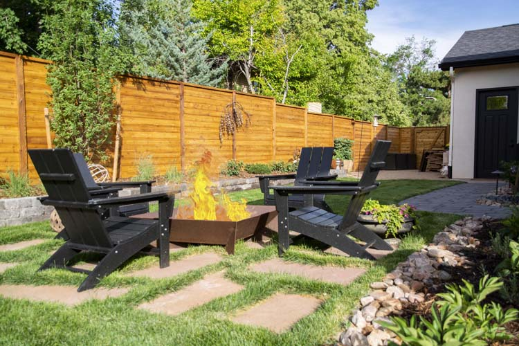 Square copper fire pit with four black adirondack chairs and paver patio
