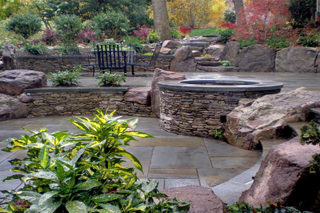 Horizon Landscaping planned and implemented this hardscape with rock walls, large boulders and stone fire pit
